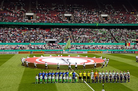 SC Sand und VfL Wolfsburg auf dem Rasen vor Logo und Zuschauerkulisse, © Maren Wuch