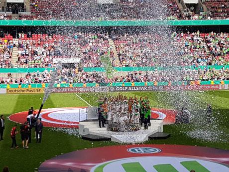 VfL Wolfsburg auf Siegertreppchen im silbernen Konfettiregen vor Zuschauertribüne, © Maren Wuch