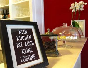 """Theke Sister Grimm mit Schild """"Kein Kuchen ist auch keine Lösung"""" und zwei gläsernen Schalen"""
